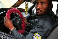 A police driver shows off his fluffy pink steering wheel cover and plastic grapes hanging from the revision mirror
