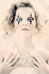 Young blonde female with large necklace and clown makeup on eyes