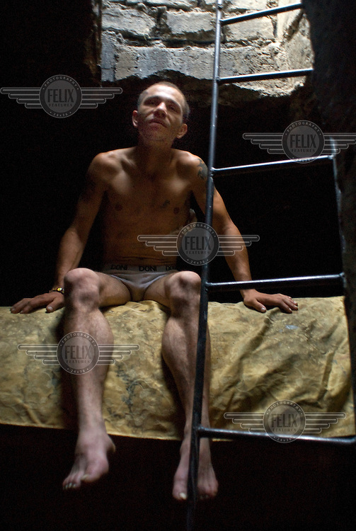 26-year-old Danila sits on a water pipe below ground in the sewerage system where he lives. He is a heroin addict and begs to fund his habit. He has a dressing on his body covering a wound received in a fight over drugs with another homeless man.