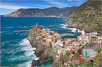A few hours after sunrise, the skies are blue across the Cinque Terre. In this image of Vernazza looking north over the Ligurian Sea, you can see the town of Monterosso al Mare in the distance. In the foreground is the watchtower for the village of Venrazza, along with the colorful homes and buildings that make up this wonderful area.