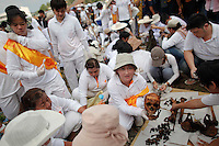 A woman holds a skull as unclaimed human remains are cleaned after being taken out of graves during a Thai Chinese ceremony at the Mang Teung Sua Jung Cemetery in Chonburi province southeast of Bangkok March 18, 2012. Every 10 years, hundreds of people wearing white, a customary colour for funerals and visiting temples, gather at this cemetery to exhume and cremate corpses as they believe they are helping the dead who have no friends or relatives. The ashes of the unclaimed bodies are spread on the sea to make room at the burial ground for more unclaimed bodies in the coming years. The tradition originated 90 years ago after diseases like Malaria killed many Thais of Chinese descent living in Chonburi.  REUTERS/Damir Sagolj (THAILAND)