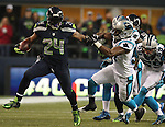 Seattle Seahawks Marshawn Lynch (24) runs through the Carolina Panthers defenders Luke Kuechly (59) and Thomas Davis (58) enroute to a 25-yard gain in the Seattle Seahawks Marshawn Lynch (24) runs through the Carolina Panthers defenders Luke Kuechly (59) Thomas Davis (58) and Adarius Glanton (57)enroute to a 25-yard gain in the NFC Western Division Playoffs at CenturyLink Field  on January 10, 2015 in Seattle, Washington. The Seahawks beat the Panthers 31-17. ©2015. Jim Bryant Photo. All Rights Reserved.