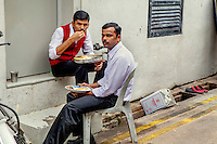 Bangladeshi staff eat a meal in an alleyway behind the restaurant where they work.