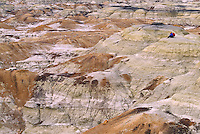 A hiker sits amid the colorful soil formations at the Bisti Wilderness Area near Farmington, NM