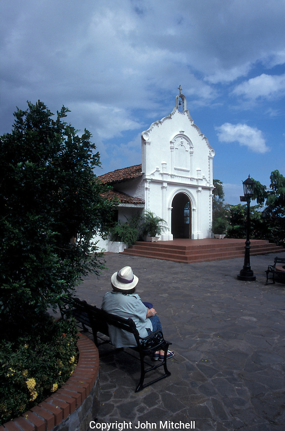 White church and woman tourist wearing a Panama hat at Mi Pueblito, a replica of a typical rural Panamanian village, Panama City, Panama