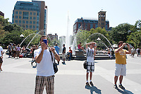 Three tourists in Washington Square Park photographing the same scene