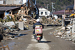 A postman on a Japan Post motorbike drives through the rubble  in Higashimatsushima, Miyagi Prefecture, Japan on  23 March 20011.  .Photographer: Robert Gilhooly