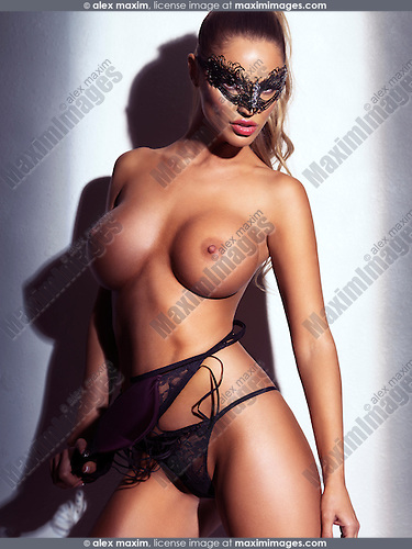 Sexy glamorous topless woman wearing a face mask. Artistic erotic photo.