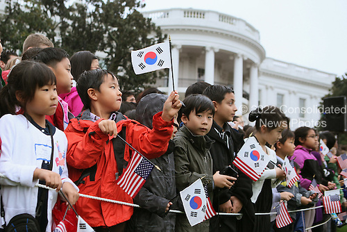 School children wave United States and Korean flags during a welcome ceremony for President Lee Myung-bak on the South Lawn of the White House, Thursday, October 13, 2011 in Washington, DC. Later in the day Lee is scheduled to hold a joint press conference with Obama and also address a joint meeting of Congress.  .Credit: Alex Wong / Pool via CNP