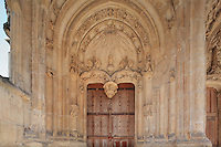 The left entrance door with angel musicians in the vaults and a sculpted tympanum representing the Annunciation, Collegiale Notre-Dame de Poissy, a catholic parish church founded c. 1016 by Robert the Pious and rebuilt 1130-60 in late Romanesque and early Gothic styles, Poissy, Yvelines, France. In the tympanum, heavenly rays reach three fleurs de lys in a vase, representing the Virgin, and the dove of the holy spirit flies along a ray. The wooden door was sculpted in 1540, and the whole entrance was restored 1999-2000. The Collegiate Church of Our Lady of Poissy was listed as a Historic Monument in 1840 and has been restored by Eugene Viollet-le-Duc. Picture by Manuel Cohen