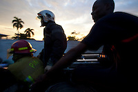 Firefighters atop a water truck in Port-au-Prince, Haiti return to the city's one fire station after arriving late to an apartment fire. Heavy traffic and narrow streets prevented the crew from getting access to a blaze at a two-story home, so the owners had to put it out themselves with water buckets. A few dozen under-equipped firefighters are tasked with providing fire service to a damaged city of over two million people.
