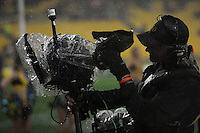 A Skysports cameraman cleans his lens in the rain. Super 15 rugby match - Crusaders v Hurricanes at Westpac Stadium, Wellington, New Zealand on Saturday, 18 June 2011. Photo: Dave Lintott / lintottphoto.co.nz