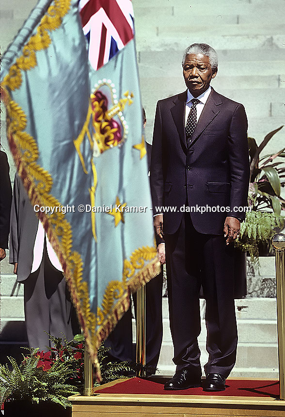 South African President Nelson Mandela stands at attention during the 1995 Commonwealth Heads of Government Meeting in Wellington, New Zealand. Mandela's attendance at the C.H.O.G.M. marked the first time South Africa had participated in the conference since leaving the Commonwealth in 1961.