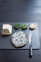A selection of goat's cheeses is served on a simple clean slate