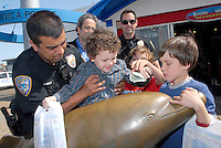 Four-year-old Santa Monica resident, Matthew Prager and  his twin brothers, 8-year-old Alex and Jacob, insert money into the  Dolphin on the Santa Monica Pier on Friday, March18, 2011.<br /> <br /> <br /> Matthew learned about homelessness for the first time in his pre-school class. He decided there and then that he wanted to do something to help. After brainstorming with his parents, he came up with the idea of selling hot chocolate to raise money. When his twin brothers Alex and Jacob heard about Matthew's idea, they wanted to get in on the action. They added the idea of selling brownies and rice crispy treats. <br /> <br /> Last weekend, they prepared homemade  rice krispies , brownies and hot chocolate and, together with their parents, sold their items outside the Santa Monica Farmer's Market and Palisades Farmer's Market. Over the course of the weekend, they sold all of their goods and raised $90. <br /> <br /> Started in 1993, the Dolphin Change Program, a project of the Bayside District Corporation, has been a way for the Santa Monica community and visitors to give responsibly to established social service organizations that help the homeless. With the help of the Marion Dorn Estate, last year's Dolphin grants totaled $50,000 dollars
