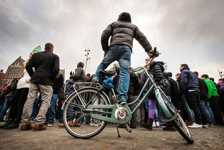 Nederland, Amsterdam, 13 dec 2014<br /> Op de Dam wordt een performance gegeven voor de toeristen. Een jongen met de fiets probeert over de rijen mensen te kijken vanaf zijn fiets.<br /> Foto: (c) Michiel Wijnbergh