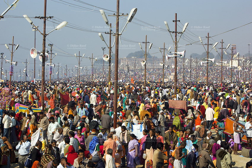 """India. Uttar Pradesh state. Allahabad. Maha Kumbh Mela. Indian Hindu devotees on the day of Mauni Amavasya Snan (Royal bath for Dark moon). The ritual """"Royal Bath"""" is timed to match an auspicious planetary alignment, when believers say spiritual energy flows to earth. The Kumbh Mela, believed to be the largest religious gathering is held every 12 years on the banks of the 'Sangam'- the confluence of the holy rivers Ganga, Yamuna and the mythical Saraswati. In 2013, it is estimated that nearly 80 million devotees took a bath in the water of the holy river Ganges. The belief is that bathing and taking a holy dip will wash and free one from all the past sins, get salvation and paves the way for Moksha (meaning liberation from the cycle of Life, Death and Rebirth). Bathing in the holy waters of Ganga is believed to be most auspicious at the time of Kumbh Mela, because the water is charged with positive healing effects and enhanced with electromagnetic radiations of the Sun, Moon and Jupiter. The Maha (great) Kumbh Mela, which comes after 12 Purna Kumbh Mela, or 144 years, is always held at Allahabad. Uttar Pradesh (abbreviated U.P.) is a state located in northern India. 10.02.13 © 2013 Didier Ruef"""