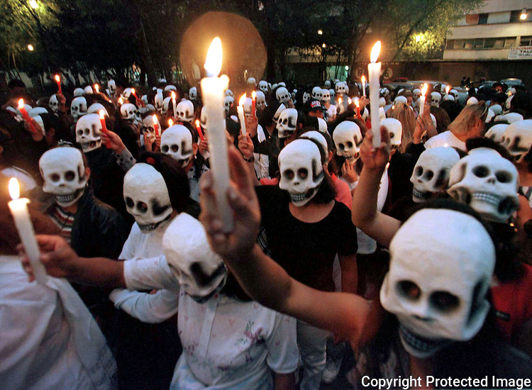 Mexican prostitutes pay homage to their dead comrades as they hold lit candles during a demonstration for the Day of the Deads in Mexico City historical centre, Novembre 1, 1996. Photo by  Heriberto Rodriguez