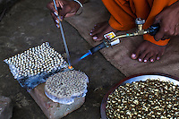 Meera makes earring parts to be sold to a manufacturer in Varanasi, Uttar Pradesh, India on 19 November 2013.