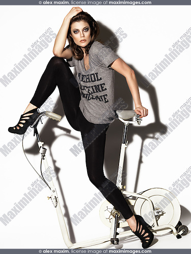 Young woman in a T-shirt and leggings posing on a retro exercise bike. Edgy high fashion photo.