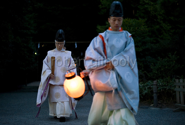 Head priest Shigeho Yoshida is led from a purification ritual in the grounds of Tsurugaoka Hachimangu shrine during he Yoimiyasai ritual that announces to the kami gods of the shrine the arrival of the upcoming Reitaisai grand festival  in Kamakura, Japan on  14 Sept. 2012.  Photographer: Robert Gilhooly