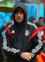 Germany coach Joachim Loew wears a raincoat before kick off but decides to remove it during the match despite heavy rain