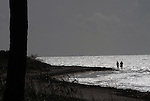 sillouetted couple walk along edge of sea in early morning on SIlver Spur Beach, Bahia Honda STate Pk, Florida Keys