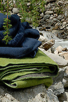 Folded blankets dyed in Nature's colours are displayed beside a rushing stream that cuts through a meadow