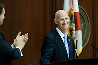 TALLAHASSEE, FLA. 3/5/13-OPENING030513CH-Gov. Rick Scott, right, receives a standing ovation from Speaker of the House Will Weatherford, R-Wesley Chapel, left, and others during the opening day of the 2013 legislative session Tuesday at the Capitol in Tallahassee, Fla...COLIN HACKLEY PHOTO