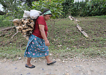 A woman walks along a road carrying firewood in Victoria 20 de enero, a village of former Guatemalan refugees in Mexico who returned home as a group in 1993, while the country's bloody civil war still raged.