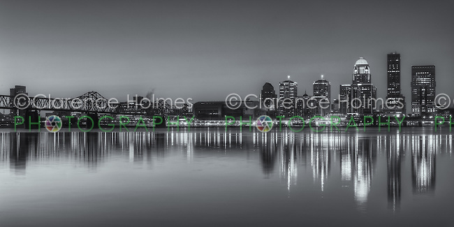 The illuminated skyline of Louisville, Kentucky, including the George Rogers Clark Memorial (Second Street) Bridge, reflects off the calm surface of the Ohio River under a clear sky during morning twilight shortly before sunrise.