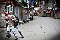 Kashmiri muslim protesters run away from stones threw by indian paramilitary soldiers in Srinagar. Outcry sparks in Nowhatta area against the detention of a kashmiri boy by police.