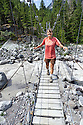 WA09943-00...WASHINGTON - Hiker on bridge crossing the Carbon River in Mount Rainier National Park. (MR# S1)