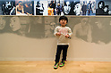SAITAMA - DEC. 5: A young Japanese child, visiting the John Lennon Museum with his parents, poses in front of photos of John Lennon and Yoko Ono.  (Photo by Alfie Goodrich/Nippon News)