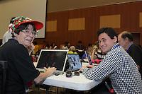 Susan Dugan and Jason Ku discuss photographs for The Daily Fold convention newsheet