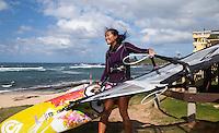 A windsurfer carries her windsurfing board towards the ocean at Ho'okipa Beach, Maui.