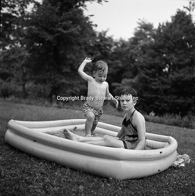 Bethel Park PA:  Michael Stewart sneaking up on the big sister Cathy in the new swimming pool - 1955