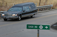 The funeral procession and hearse carrying the body of Sago miner Jesse Jones passes Sunday, Jan. 8, 2006, the road leading to the mine where he died in an explosion last Monday near Buckhannon, WV.  (Gary Gardiner/EyePush Newsphotos)<br />