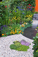 Thymus thymes herbs in gravel edged with stell circle, and steel metal edging around patio, clematis climbing on trellis wall, Tropaeolum nasturtiums, Crocosmia, Lavandula angustifolia lavender herb, Coreopsis, Fagus hedge, Alchemilla flowers, blue Salvia, Kniphofia, patio, stone wall