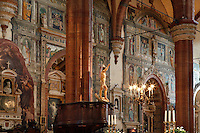 Low angle view of interior of the Duomo, or Cattedrale di Verona, S. Maria Assunta, 12th century, Verona, Italy, showing the lecturn with a statue of Christ in front of the richly painted walls. The cathedral was built in 1117-38, but the interior was remodeled in the 15th and 16th centuries, in Gothic style, with three aisles divided by tall, broad arches. Picture by Manuel Cohen.