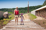 Happy Woman Walking with Kid Girl Holding Hands in Estonian Road Museum, Põlva County