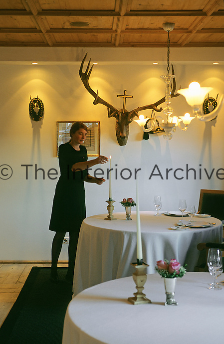 A member of staff lighting the candles for the evening meal at the Hotel & Spa Rosa Alpina