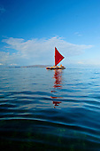 Outrigger sailing canoe with red sail, Wailea, Maui