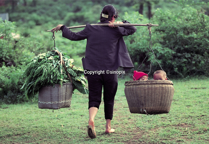 A mother carries vegetables in one basket and children in another as she leaves the fields in Guangzhou, China.