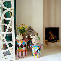 Moroccan side tables painted in a harlequin pattern display a Syrian oil lamp and a Mauritian basket beside the fireplace in the bedroom