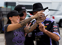 Aug 31, 2014; Clermont, IN, USA; NHRA funny car driver Alexis DeJoria (left) talks a selfie photo with father John Paul DeJoria (right) and race fan Josh Givens during qualifying for the US Nationals at Lucas Oil Raceway. Mandatory Credit: Mark J. Rebilas-USA TODAY Sports