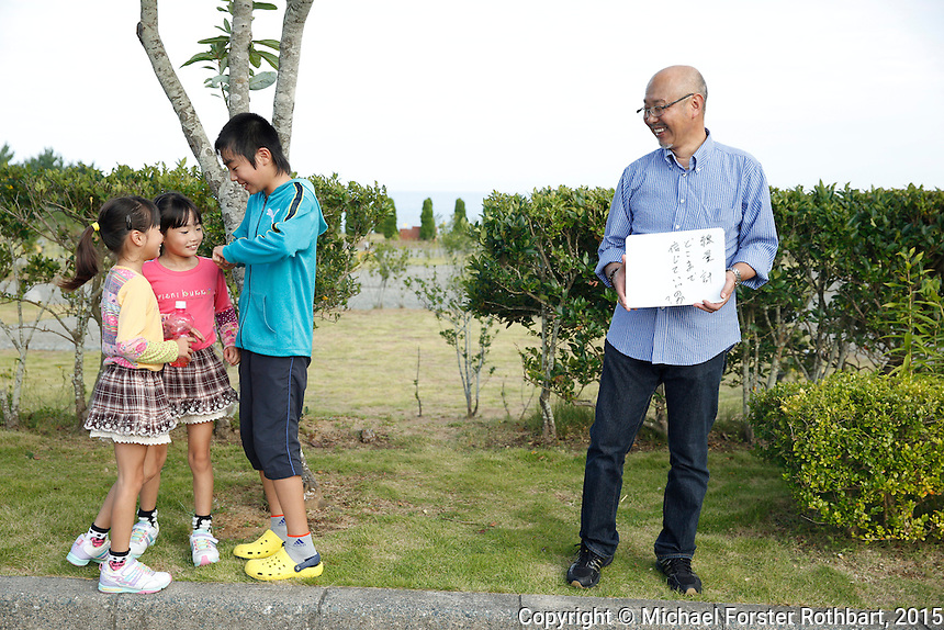 Masatoshi Ohata is an engineer working to design robots that will decontaminate the inside of the Fukushima Daiichi plant. He lives in Iwaki but has brought his grandchildren, ages 7 and 11, to go biking at a seaside park in Naraha. His wife, Kumiko Ohata, believes this visit should be safe as long as their stay does not exceed three hours. <br /> <br /> Masatoshi writes, &ldquo;Please do not forget about the people who are suffering from the damages by tsunami.&rdquo; As the family walks to their car, he explains the concerns he alluded to: evacuees from the nuclear exclusion zone receive a lot of attention and a high amount of benefits, including free housing and compensation for their losses and &ldquo;mental anguish&rdquo;; however, evacuees who lost homes directly from the natural disaster are neglected and receive almost no support.<br /> <br /> In March 2011, an earthquake and tsunami hit northern Japan and destroyed the Fukushima Daiichi nuclear power plant. Some 488 thousand people evacuated from the three-part disaster; in 2015, nearly 25% remain displaced.<br /> <br /> A massive effort is now underway to decontaminate towns in the Fukushima Exclusion Zone. In Tomioka, 5 to 8 miles from the nuclear plant, thousands of laborers are cleaning or demolishing every building, and removing and incinerating all topsoil in inhabited areas. In the adjacent forests and mountains, radiation levels remain higher and will not be cleaned.<br /> <br /> Naraha, 12 miles south of the nuclear plant, is the first town to reopen after the disaster. Residents were allowed to return home full-time on Sept. 5, 2015. To date, an estimated 440 residents have returned, out of a pre-disaster population of 7,400. <br /> <br /> I returned to Fukushima one week after Naraha reopened and spent a month there, interviewing and photographing returnees and decontamination workers. I asked portrait subjects to write down their hopes and fears for their hometowns, and then discuss these though