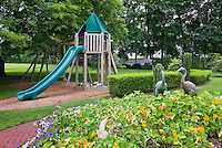 Kids backyard near garden, with tree house, sliding board, tiered plantings of petunias &nasturtiums, trees, shade, swings, boxwood, lawn, great family backyard