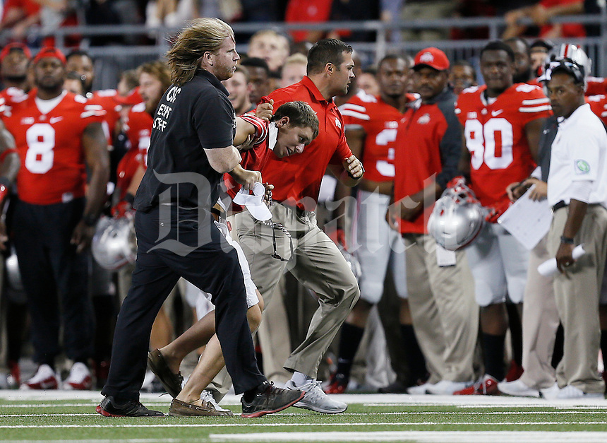 Ohio State Buckeyes coach Anthony Schlegel and a security guard wrestle a student off the field in the second quarter of the college football game between the Ohio State Buckeyes and the Cincinnati Bearcats at Ohio Stadium in Columbus, Saturday afternoon, September 27, 2014. The Ohio State Buckeyes defeated the Cincinnati Bearcats 50 - 28. (The Columbus Dispatch / Eamon Queeney)