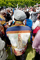 "Switzerland. Canton Valais. St-Maurice. Africa Saints Pilgrimage (Pèlerinage aux Saints d'Afrique). Various religious choirs coming from allover Switzerland sing and celebrate their faith and belief in Jesus  Christ. A man wears a shirt with drawing of ""Our Lady of Fátima "" a title for the Virgin Mary due to her reputed apparitions to three shepherd children at Fátima, Portugal in 1917. The title of Our Lady of the Rosary is also sometimes used to refer to the same apparition. According to religious tradition, Mary was an Israelite Jewish woman and the mother of Jesus. Among her many other names and titles are the Virgin Mary or Blessed Virgin Mary, Mother of God, and Saint Mary in Western churches, Theotokos in Orthodox Christianity, and Maryam, mother of Isa in Islam. The first part of the pilgrimage takes place in Véroliez which is a part of the town of St-Maurice. 2.06.13 © 2013 Didier Ruef"